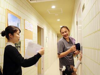 宿泊客に積極的に働きかけて参加を呼びかけるインターン生